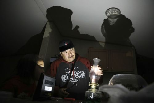 Jimmie Long Jr. places the glass on an oil lamp inside his Kaibeto home on the Navajo Reservation in Arizona.