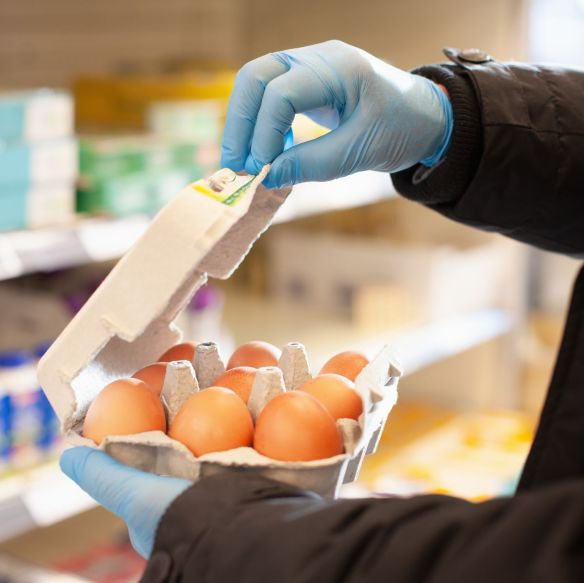 Man shopping for eggs at supermarket, wearing protective gloves